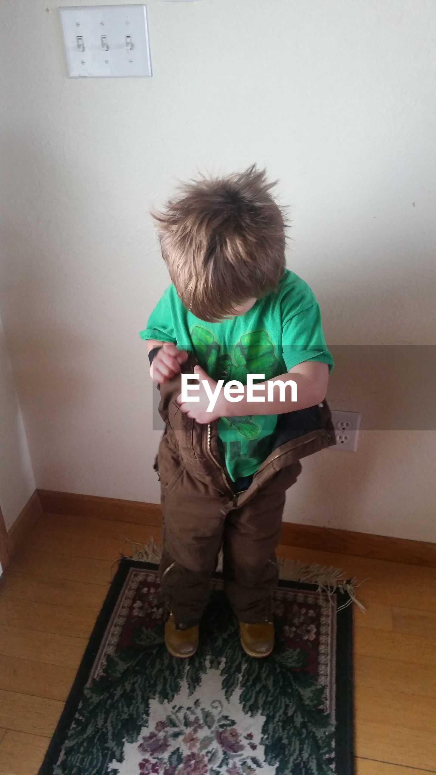High angle view of boy wearing cloth at home