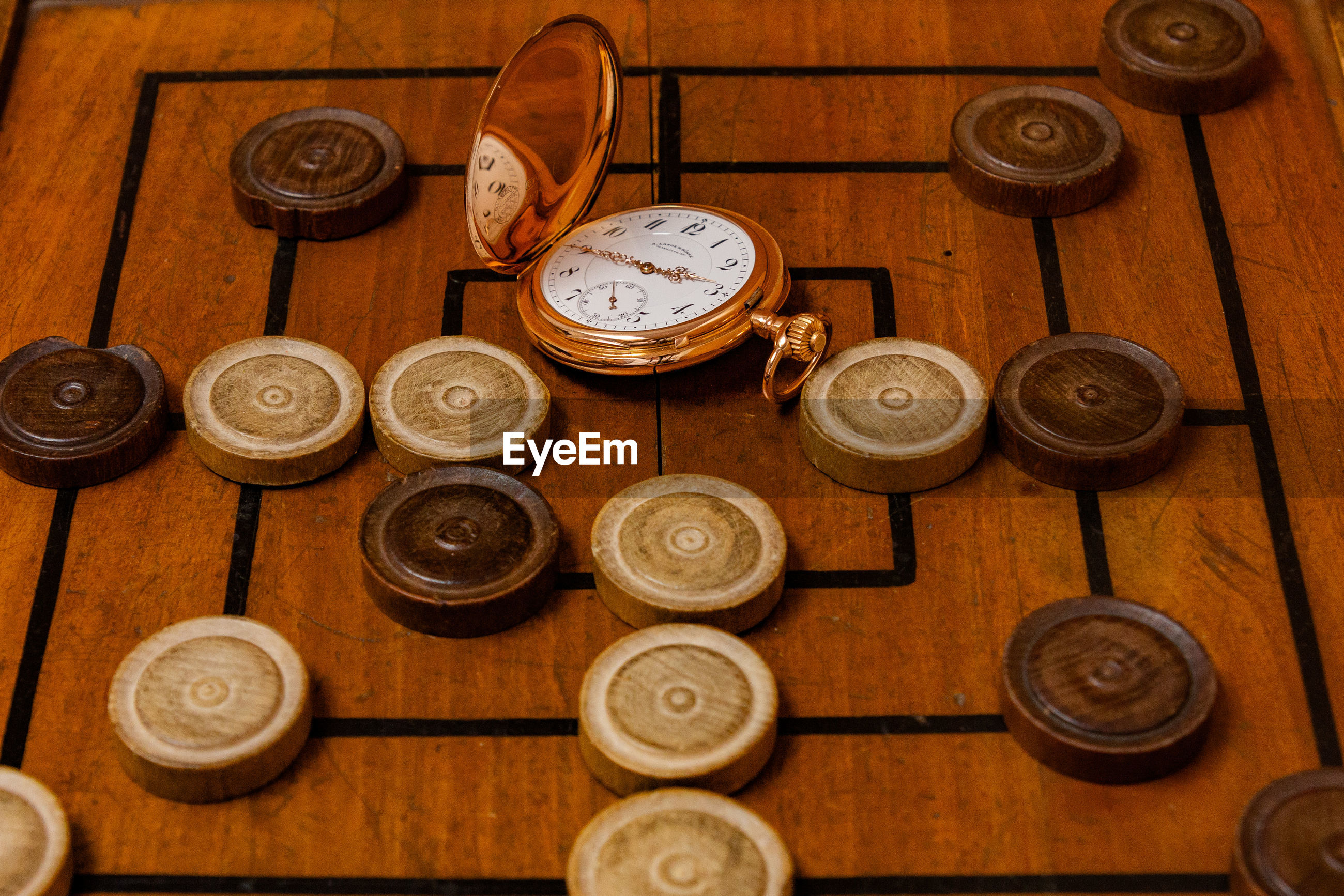 High angle view of pocket watch and board game