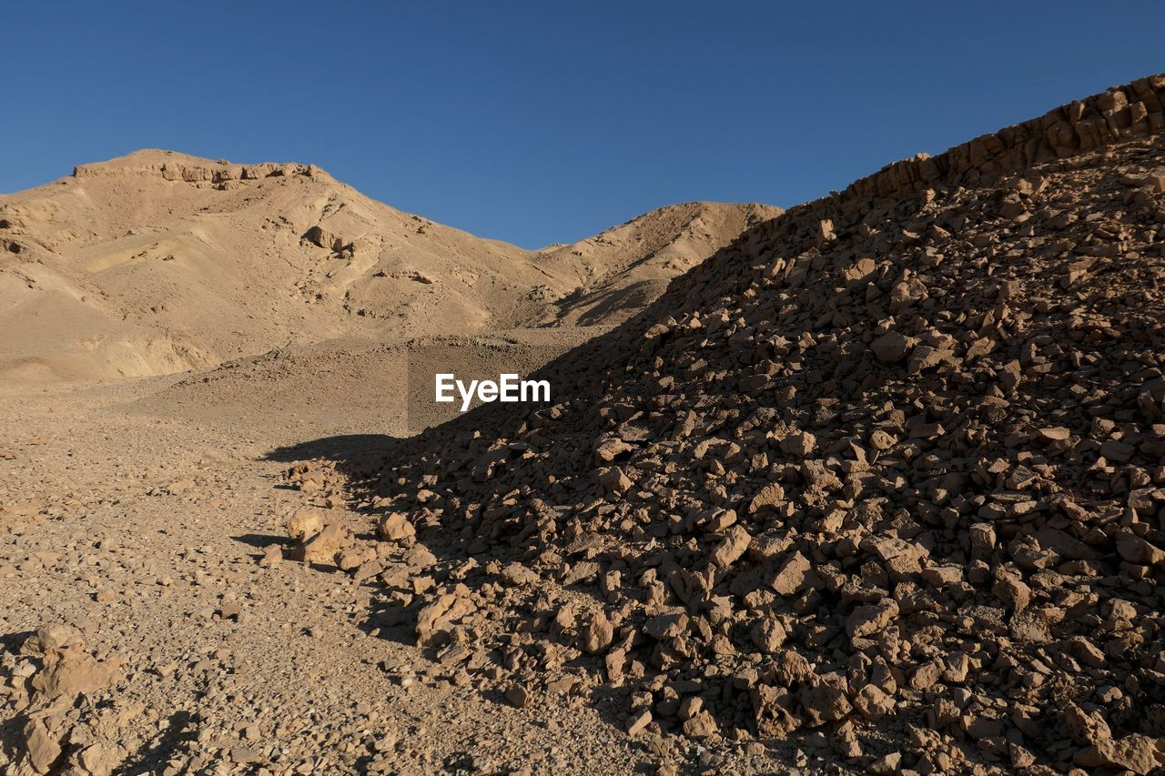 sky, nature, clear sky, mountain, land, tranquility, scenics - nature, rock, tranquil scene, desert, no people, solid, landscape, beauty in nature, day, arid climate, geology, non-urban scene, rock - object, extreme terrain, climate, outdoors, formation, eroded, mountain peak