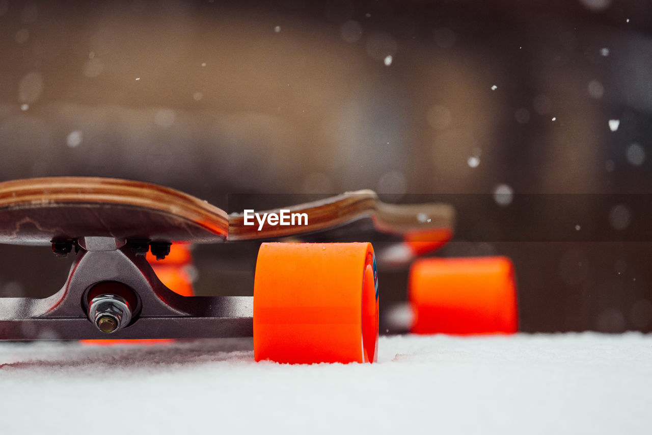 orange color, snow, close-up, no people, focus on foreground, cold temperature, transportation, winter, car, selective focus, mode of transportation, indoors, motor vehicle, day, toy car, nature, still life, metal, snowing