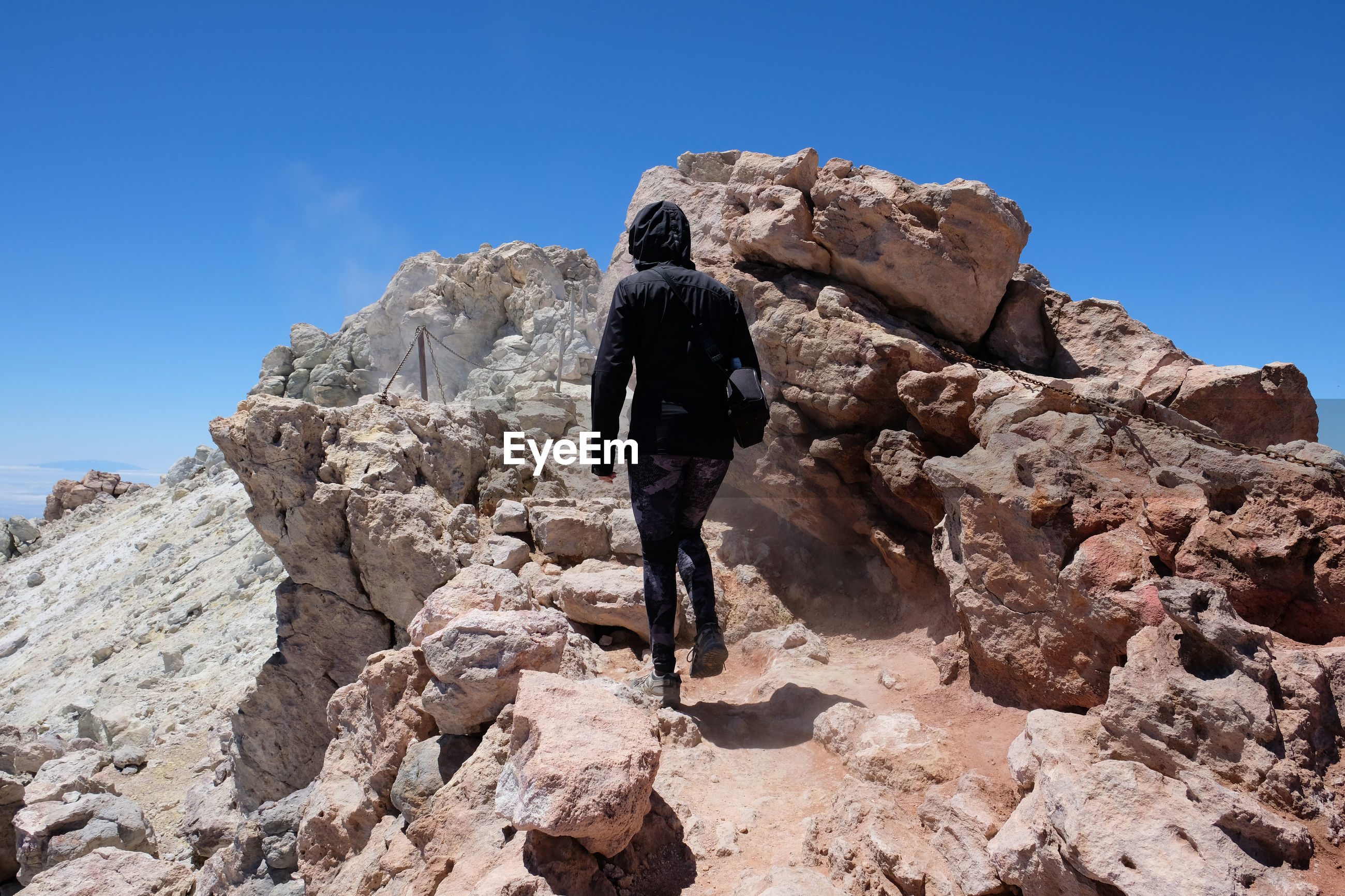 Rear view of woman walking by rock formation against sky