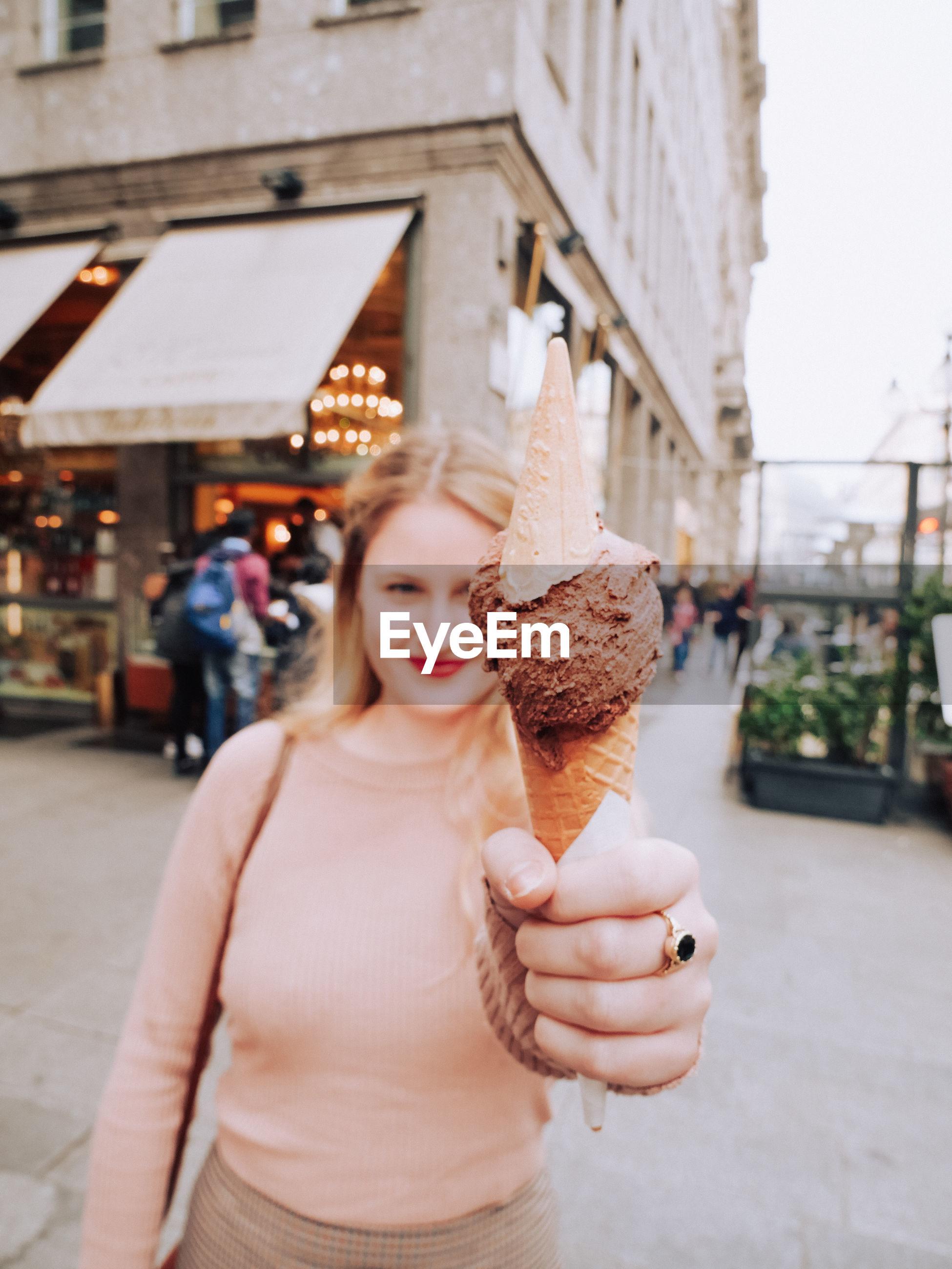 Portrait of woman holding ice cream on footpath