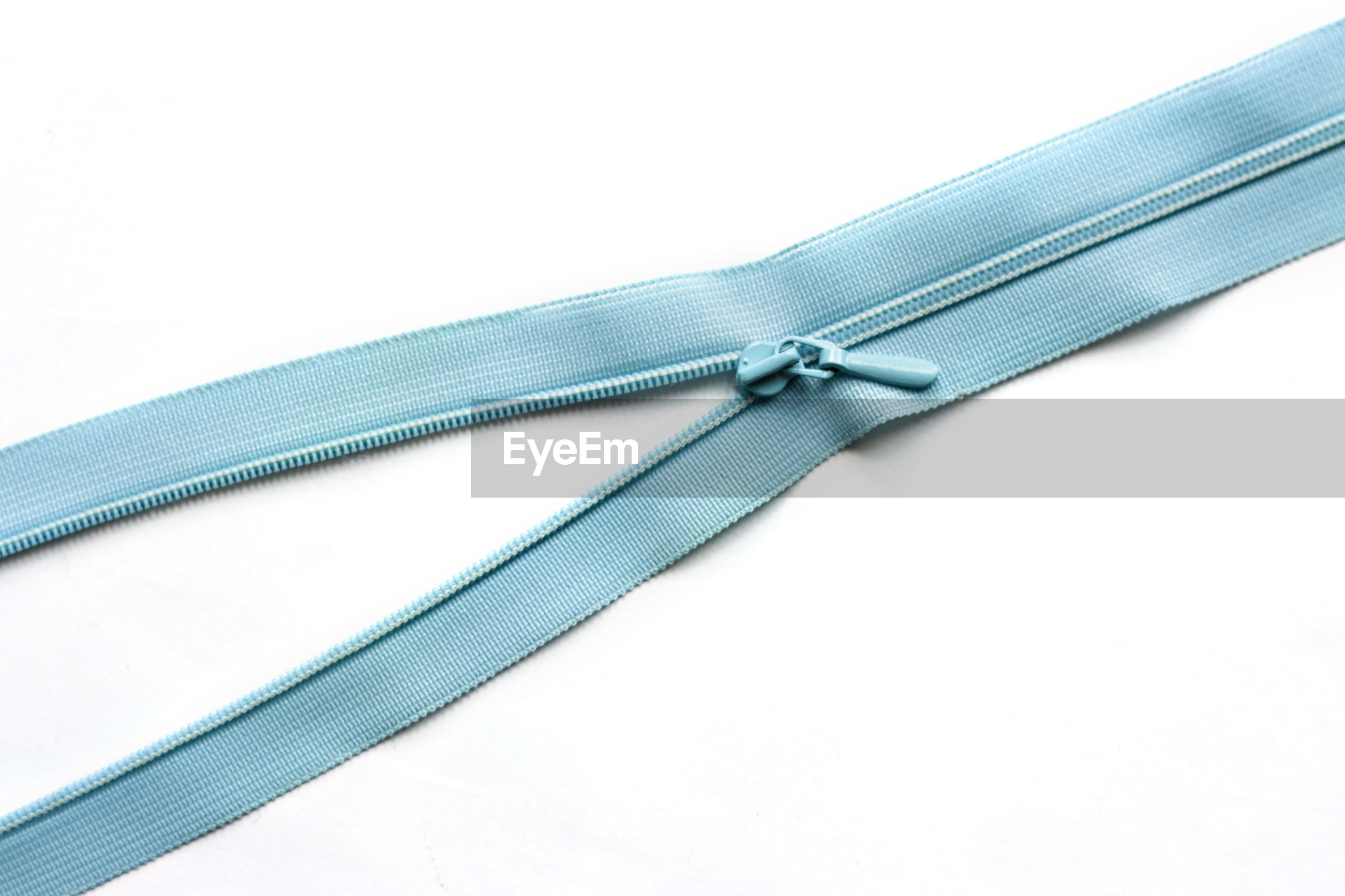 Close-up of blue zip chain over white background