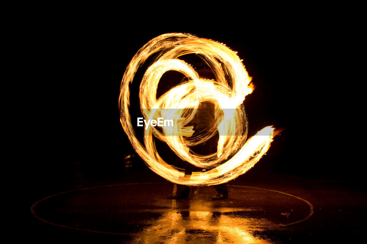 motion, burning, fire, fire - natural phenomenon, heat - temperature, night, long exposure, nature, water, glowing, reflection, flame, illuminated, blurred motion, spinning, copy space, black background, indoors, light painting, dark, wire wool