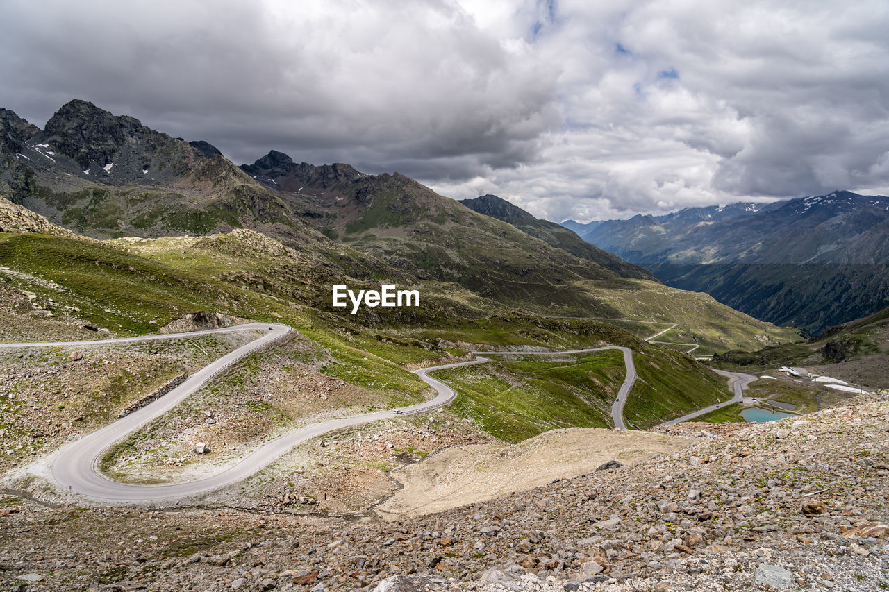 AERIAL VIEW OF ROAD BY MOUNTAINS AGAINST SKY
