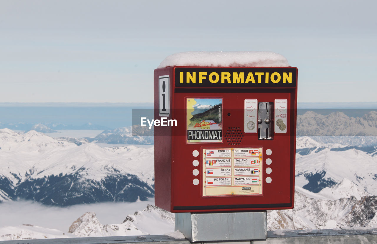Coin-Operated Information Equipment Against Snowcapped Mountain