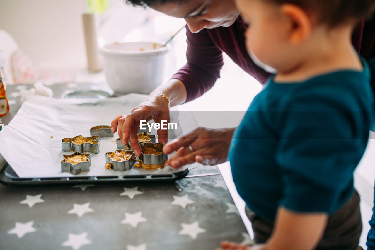 real people, child, men, childhood, males, boys, indoors, selective focus, leisure activity, lifestyles, food and drink, two people, holding, table, food, women, offspring, plate, tray, glass