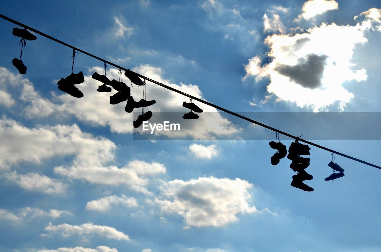 cloud - sky, sky, low angle view, nature, silhouette, hanging, no people, outdoors, day, cable, shoe, animal, sunlight, group of animals, air vehicle, beauty in nature, electricity, arts culture and entertainment, vertebrate
