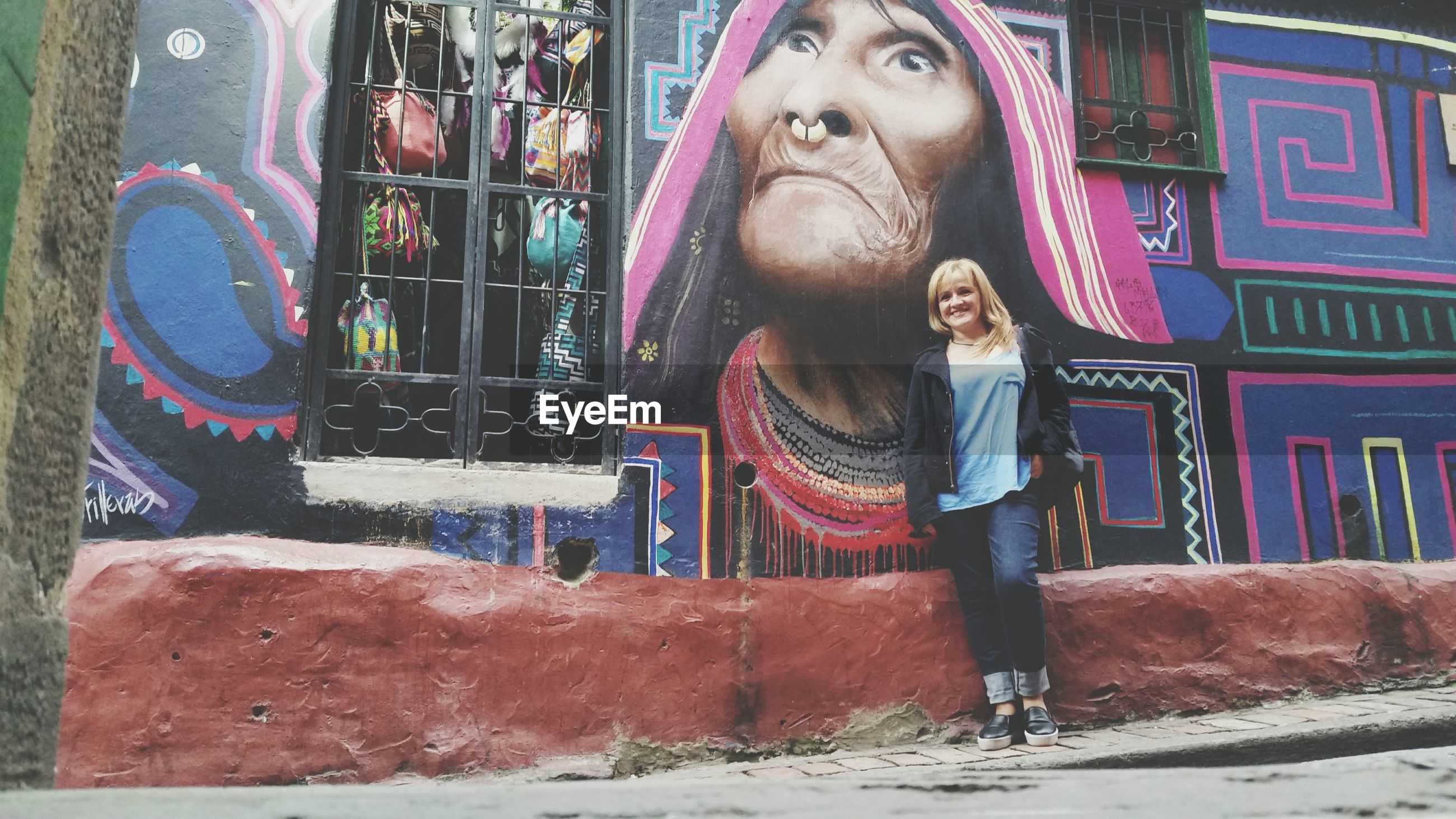 Full length portrait of smiling woman standing by graffiti on wall