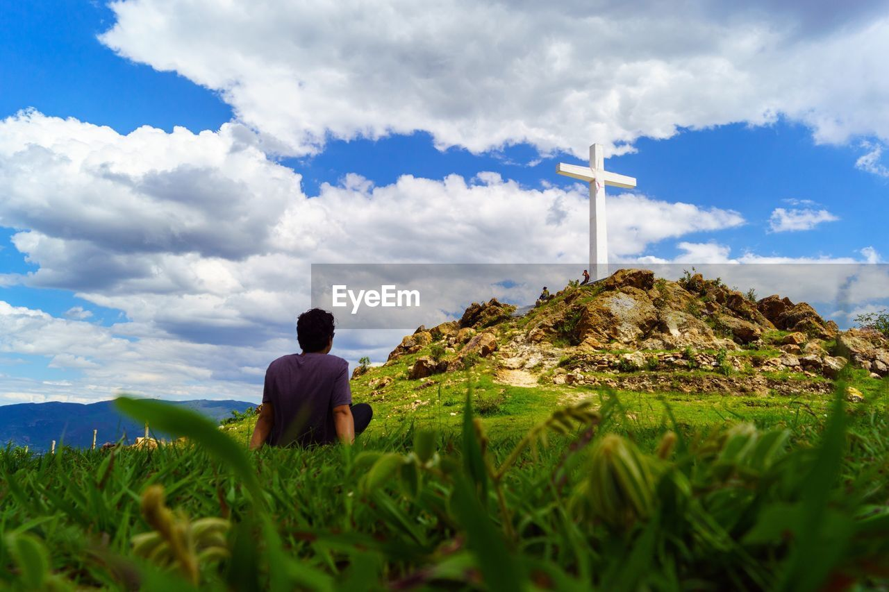 cloud - sky, sky, rear view, one person, beauty in nature, nature, real people, mountain, men, scenics - nature, rock, tranquility, sitting, leisure activity, day, lifestyles, plant, land, non-urban scene, outdoors