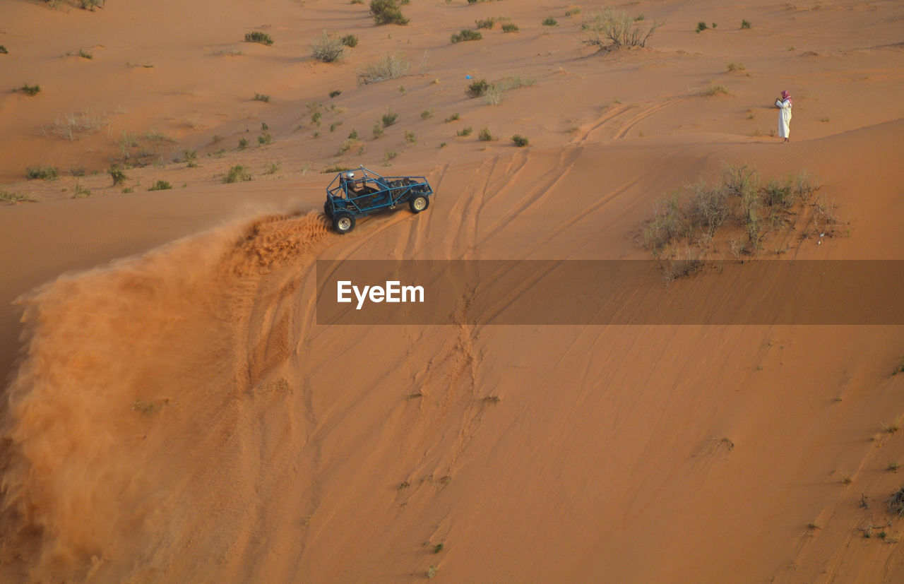 High Angle View Of Man And Off-Road Vehicle At Desert