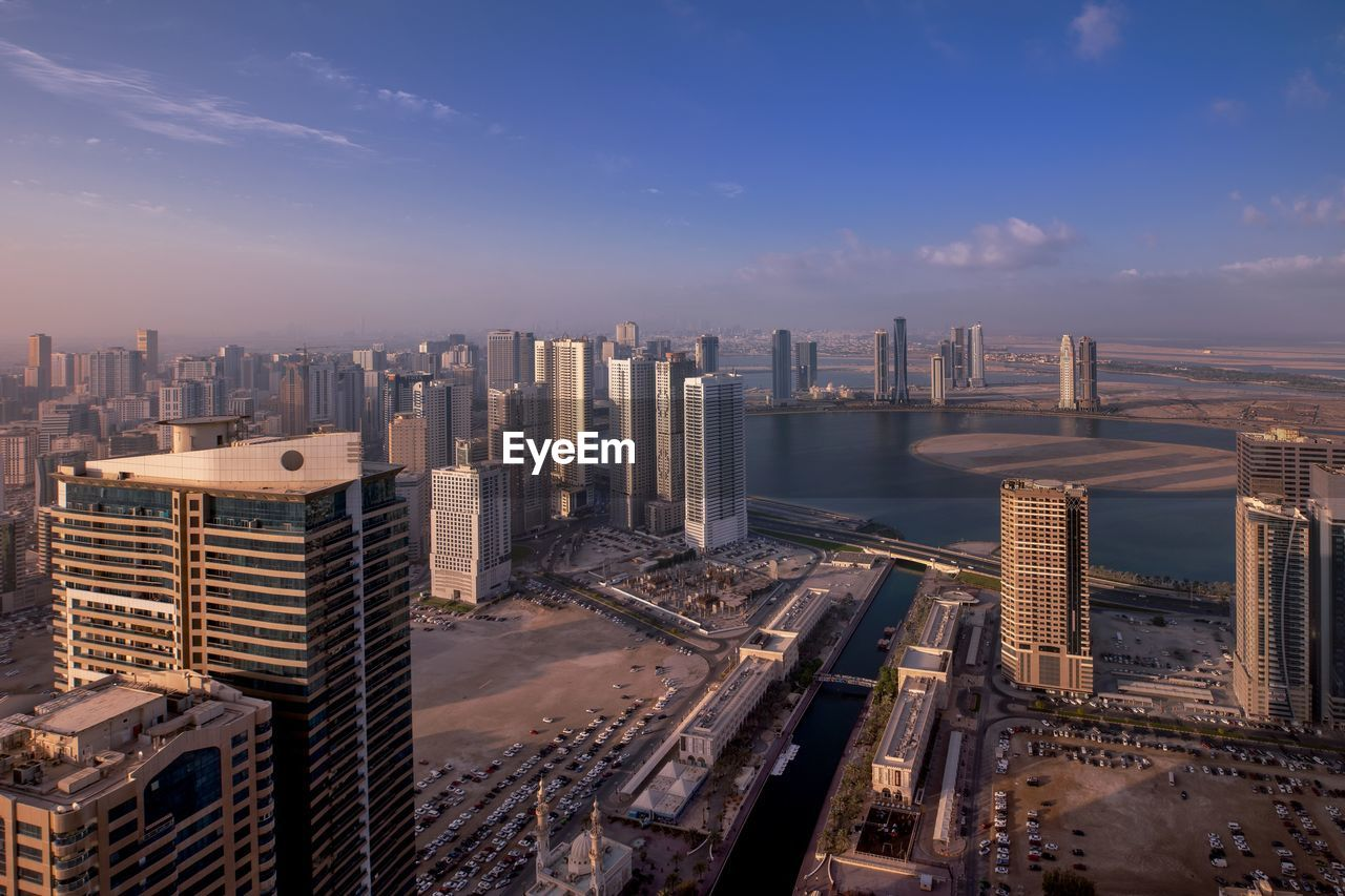 cityscape, sky, building exterior, built structure, city, architecture, office building exterior, skyscraper, building, tall - high, urban skyline, modern, cloud - sky, tower, nature, water, residential district, landscape, high angle view, no people, outdoors, financial district, spire