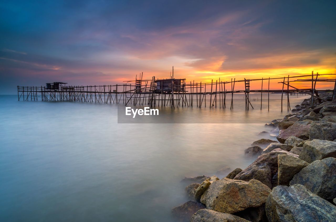 sky, sunset, water, scenics - nature, beauty in nature, sea, cloud - sky, tranquil scene, orange color, tranquility, rock, idyllic, nature, pier, rock - object, solid, no people, architecture, built structure, outdoors