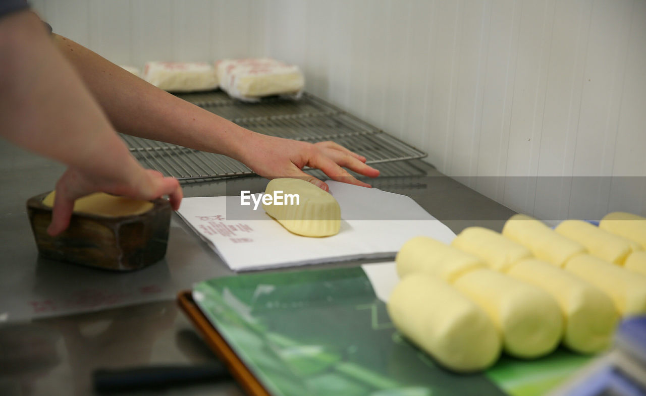 Close-up of hands wrapping butter