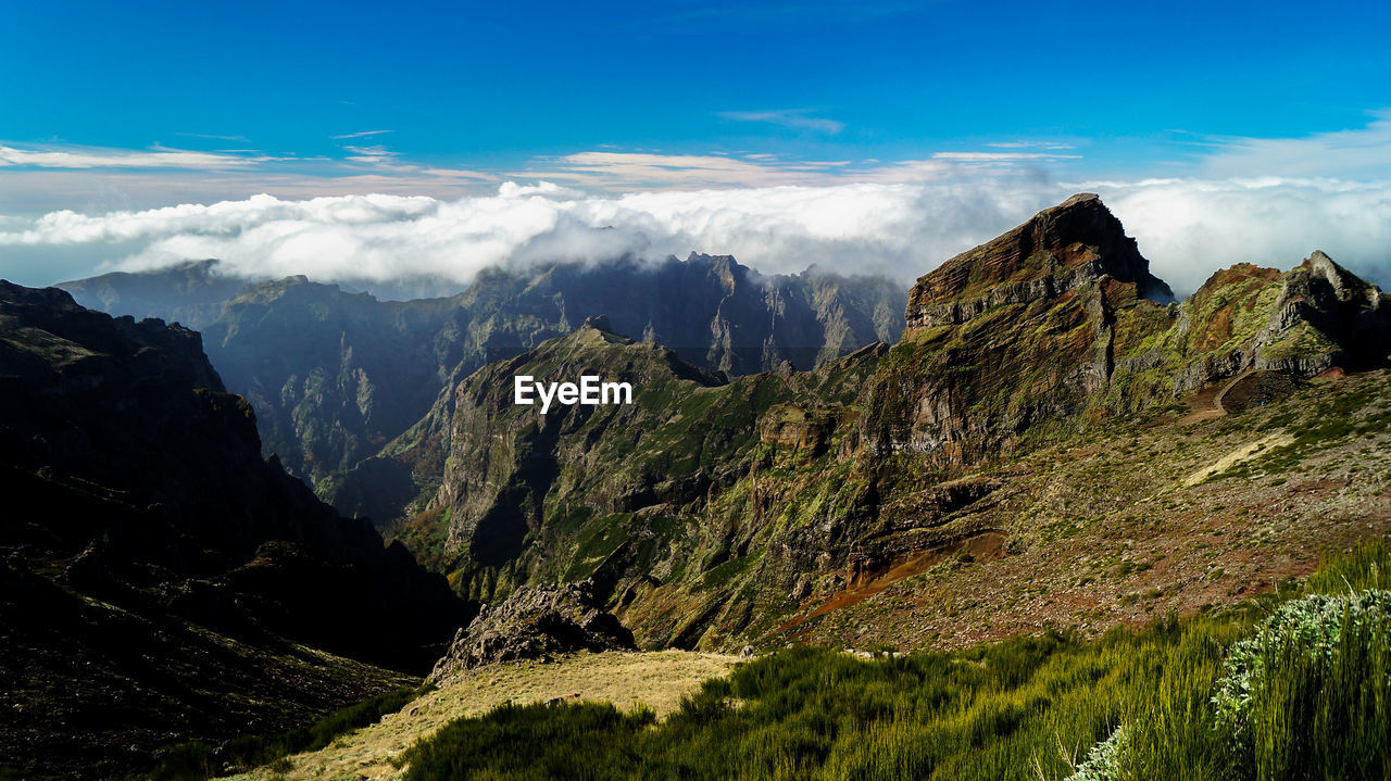 Scenic view of mountains against cloudy blue sky