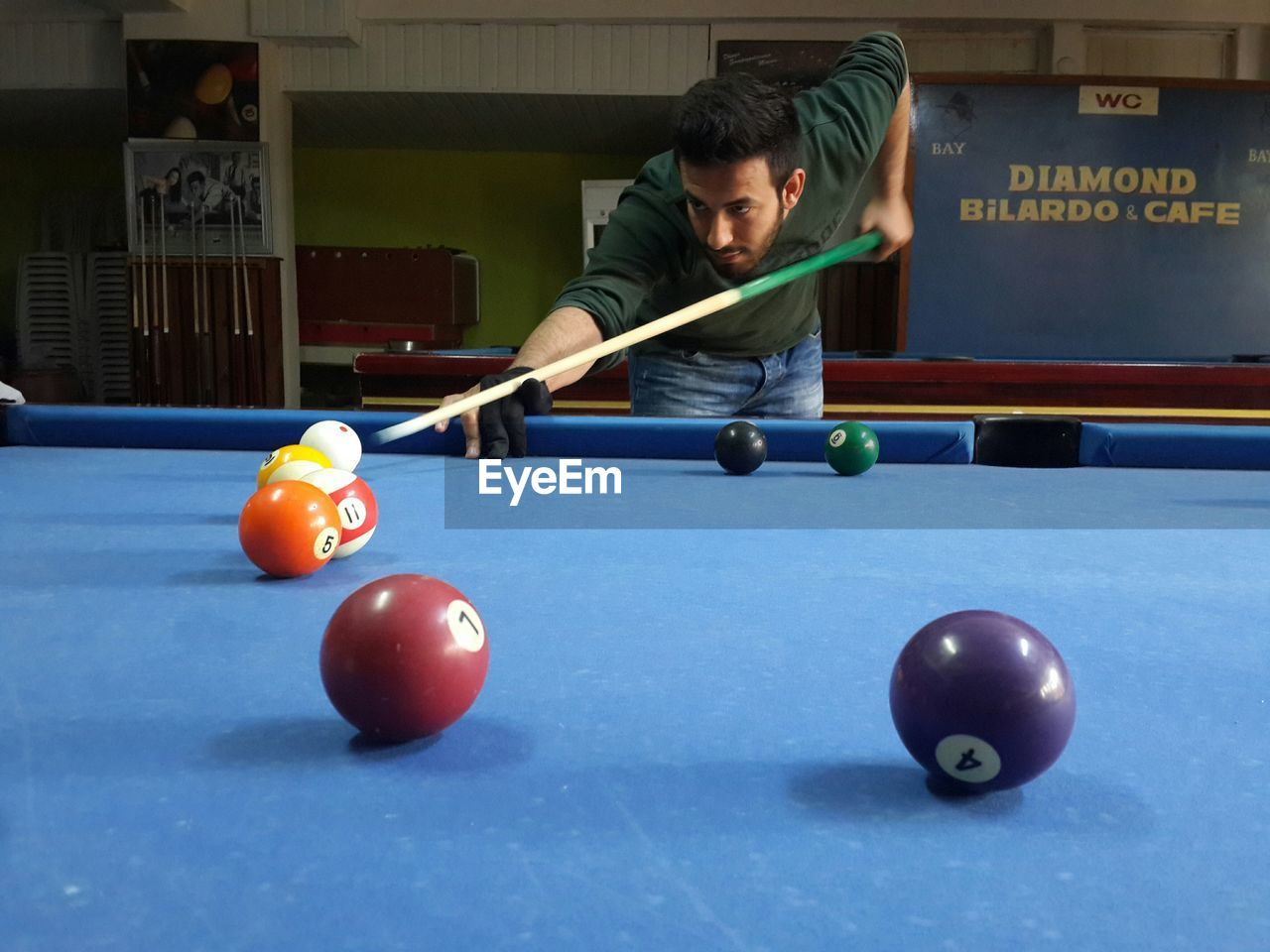 pool ball, pool table, pool - cue sport, playing, real people, one person, leisure activity, pool cue, sport, snooker, indoors, ball, lifestyles, snooker ball, young adult, competition, day, people