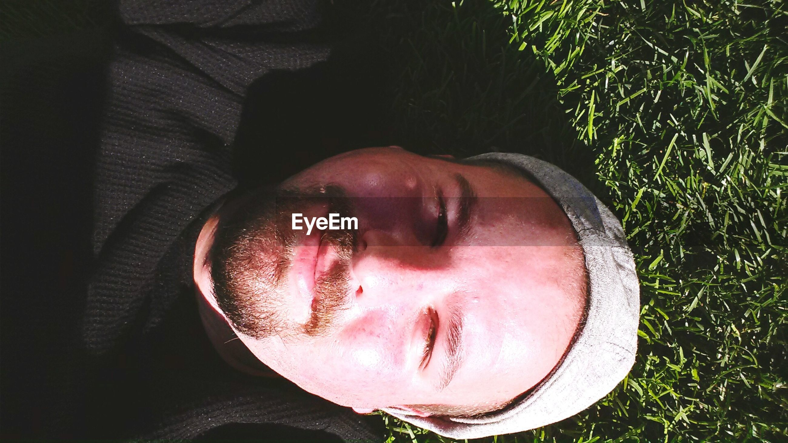 Close-up high angle view of young man lying on grass