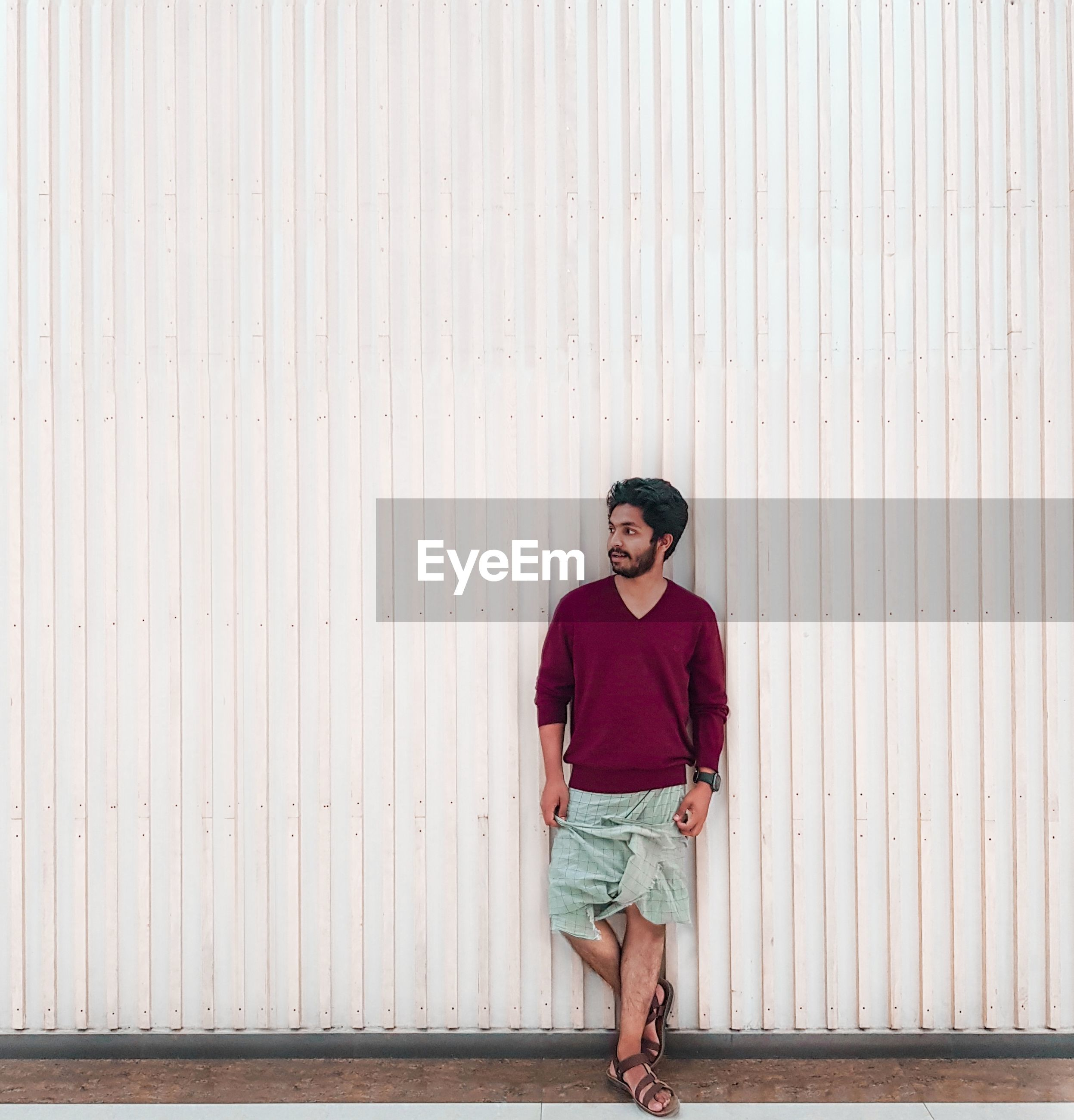 Full length of young man standing against wall