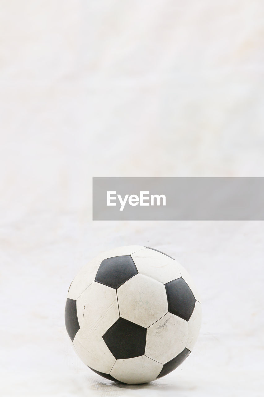 ball, soccer ball, soccer, sports equipment, team sport, sport, no people, focus on foreground, close-up, black color, still life, day, copy space, white color, indoors, high angle view, nature, single object, football