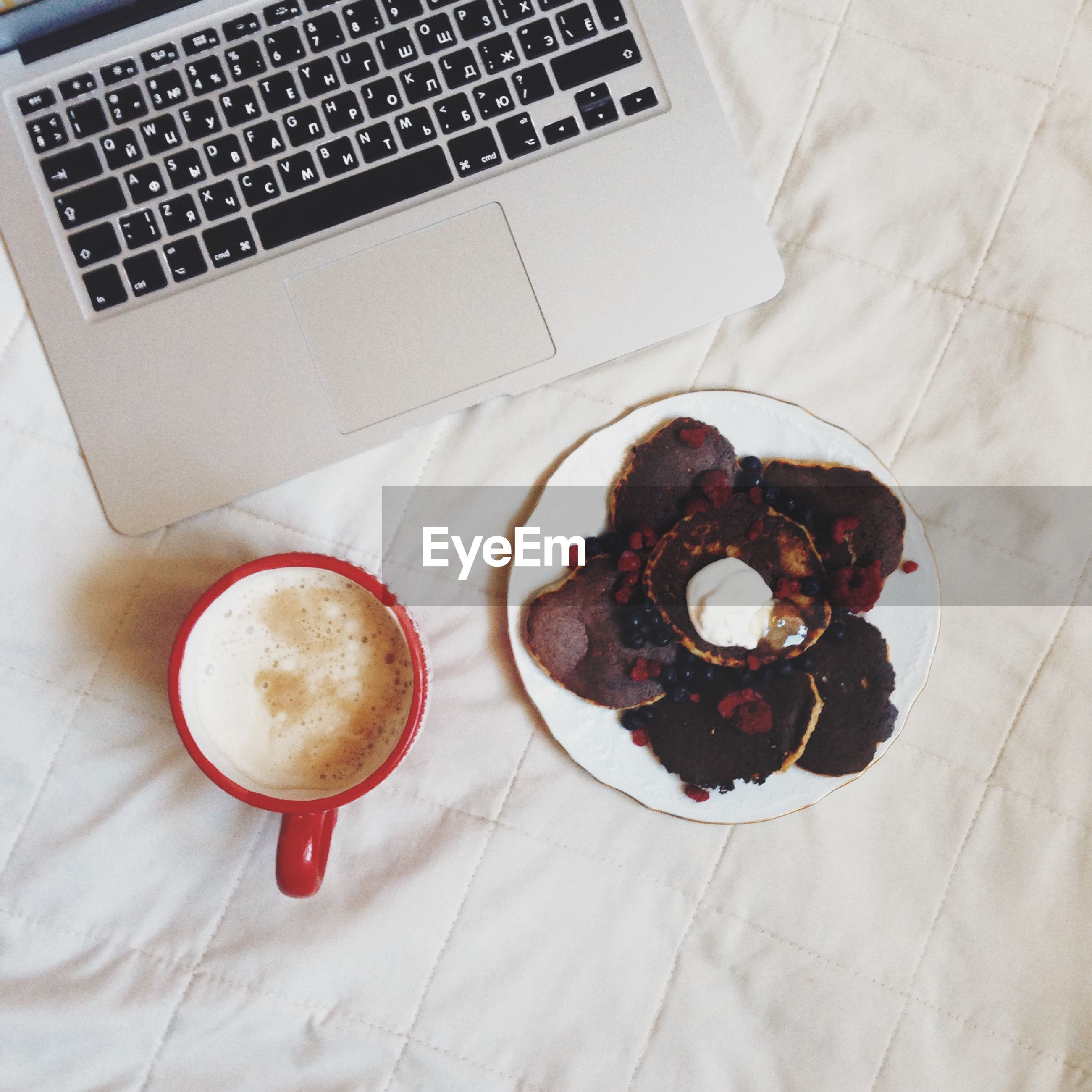 High angle view of cropped laptop with coffee and snacks