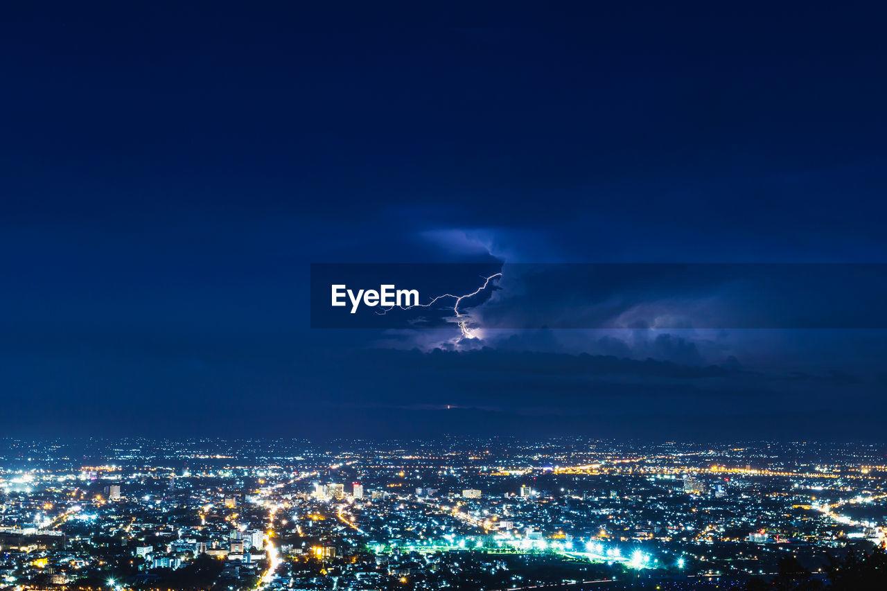 Lightning Striking Over Illuminated Cityscape At Night