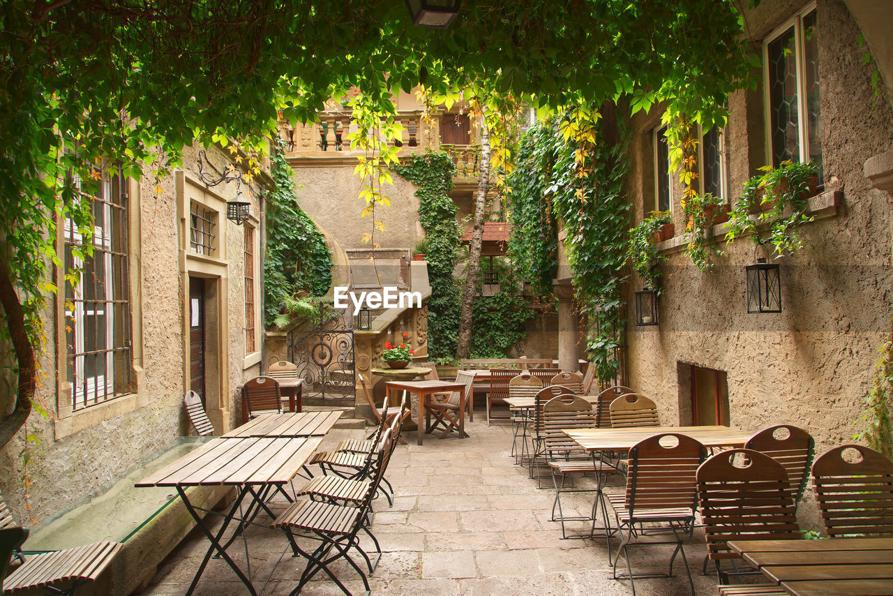 seat, architecture, built structure, chair, building exterior, plant, table, absence, tree, building, day, empty, nature, no people, cafe, city, restaurant, outdoors, bench, sidewalk cafe, setting