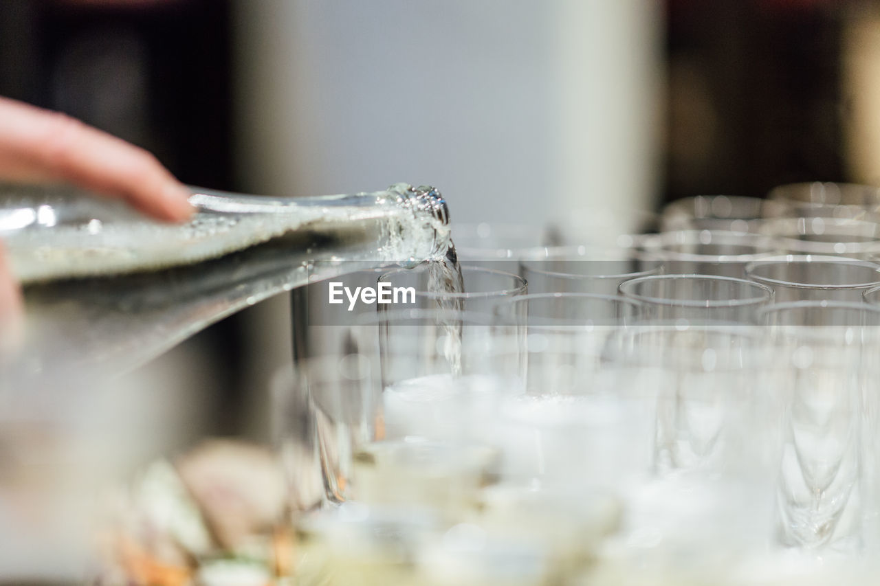 human hand, one person, hand, human body part, indoors, real people, selective focus, unrecognizable person, close-up, water, holding, food and drink, motion, glass, refreshment, drink, household equipment, focus on foreground, pouring, finger, human limb