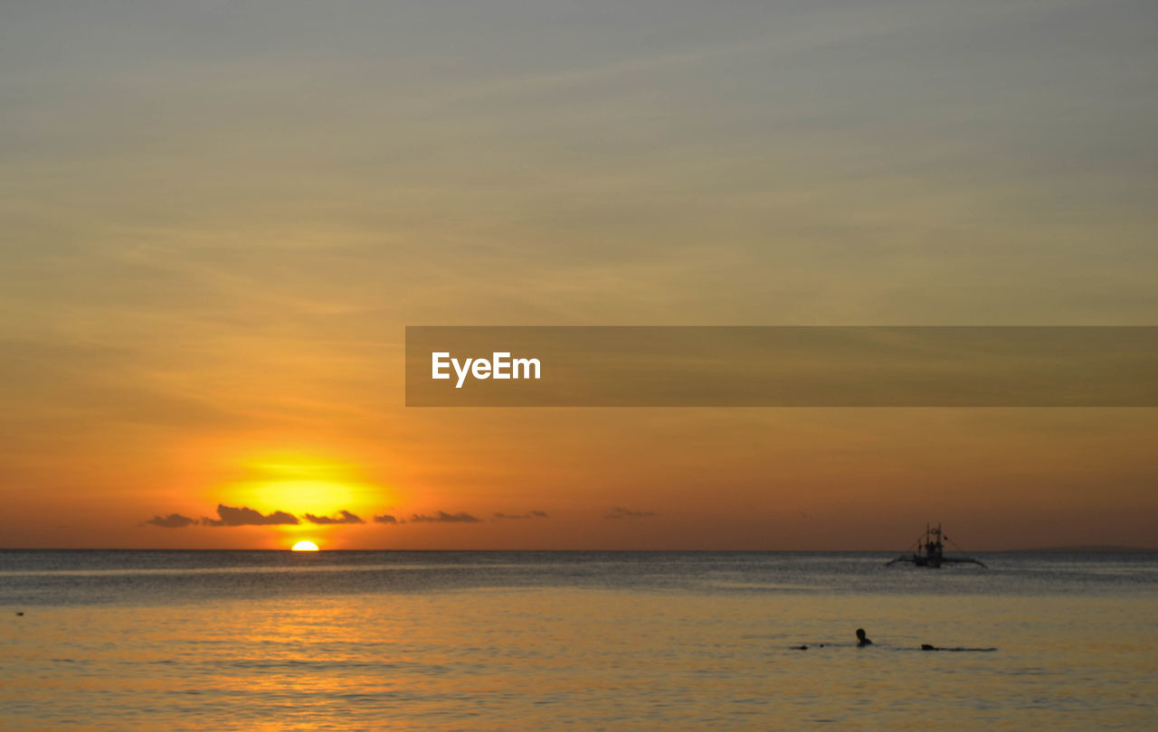 sunset, sea, beauty in nature, scenics, water, nature, silhouette, sky, orange color, sun, tranquility, tranquil scene, reflection, vacations, beach, real people, leisure activity, waterfront, outdoors, horizon over water, travel destinations, men, nautical vessel, wave, jet boat, people