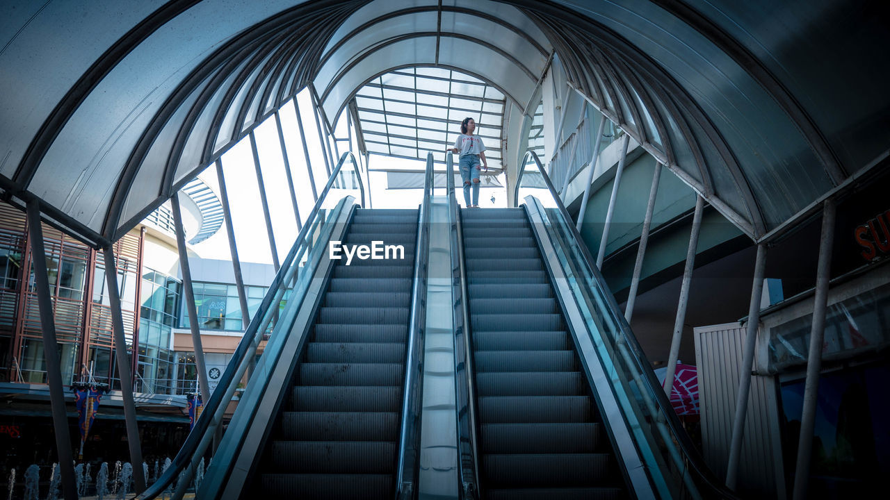 architecture, staircase, steps and staircases, built structure, modern, railing, indoors, real people, low angle view, escalator, men, convenience, day, lifestyles, incidental people, people, transportation, glass - material, ceiling