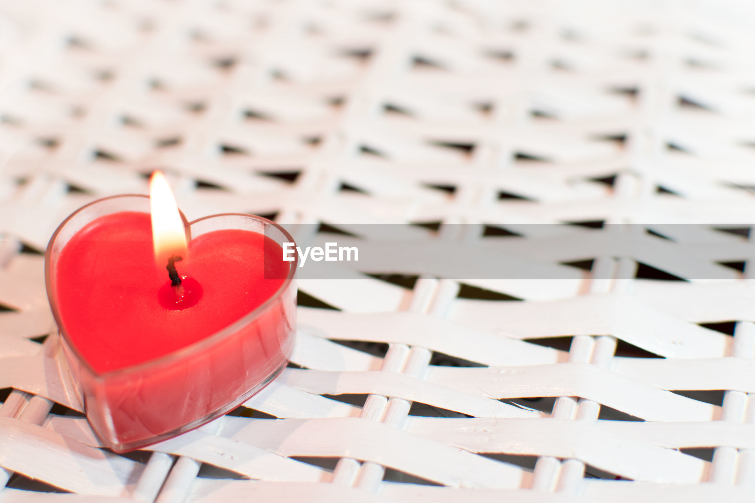 High angle view of illuminated heart shape candle on table