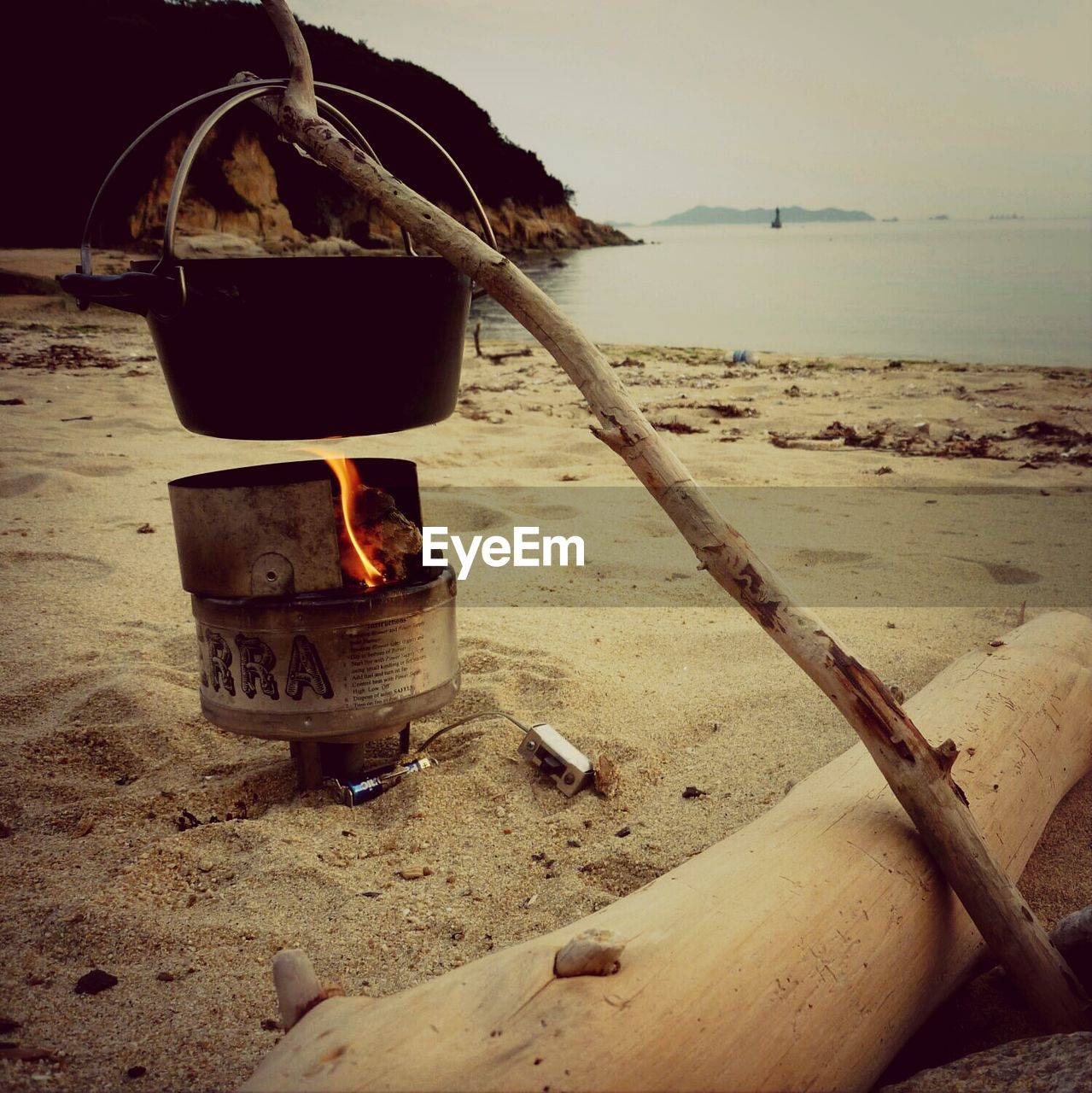 Container Hanging On Twig Above Burning Stove At Sandy Beach