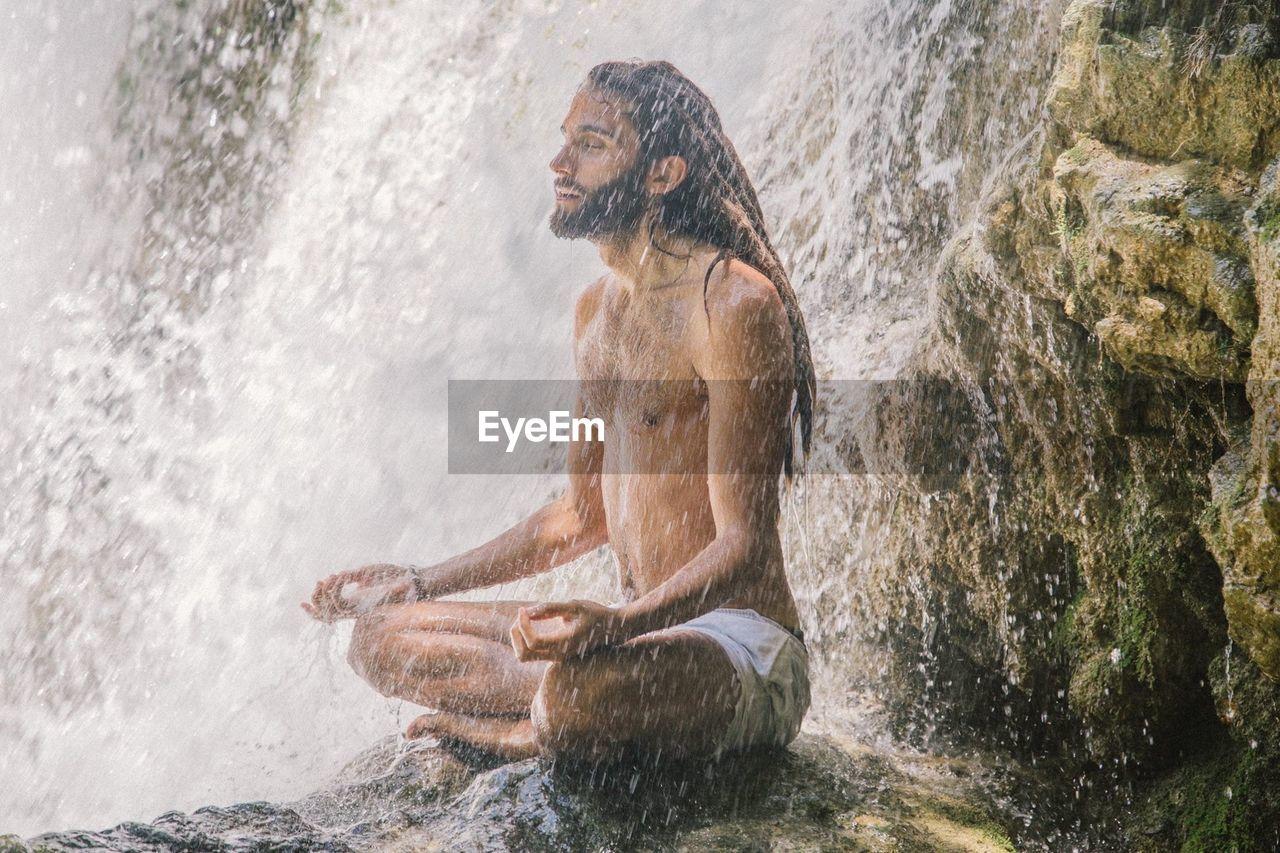 Full length of shirtless man sitting in water