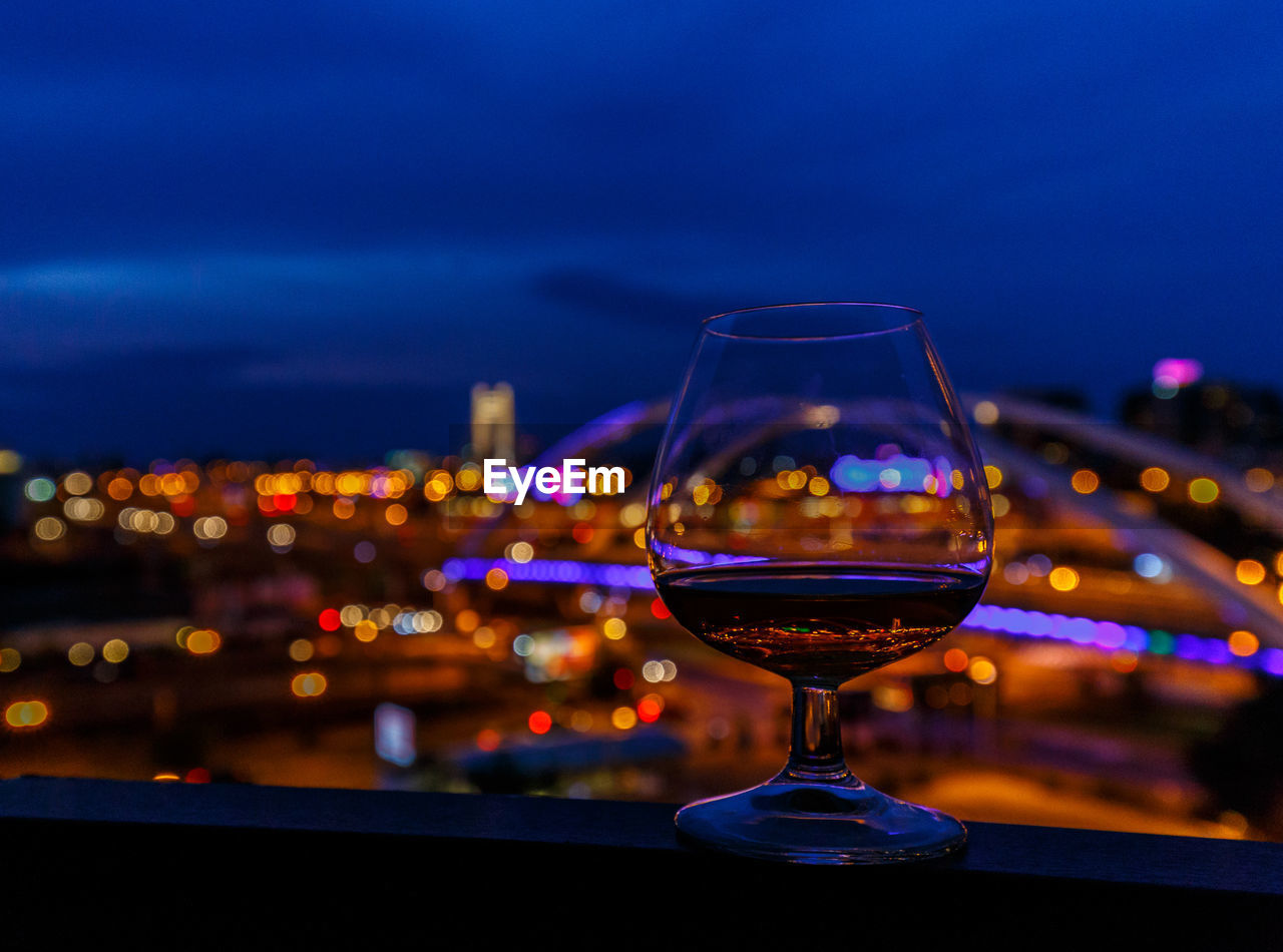Close-Up Of Wineglass On Railing By Illuminated Cityscape Against Sky At Night