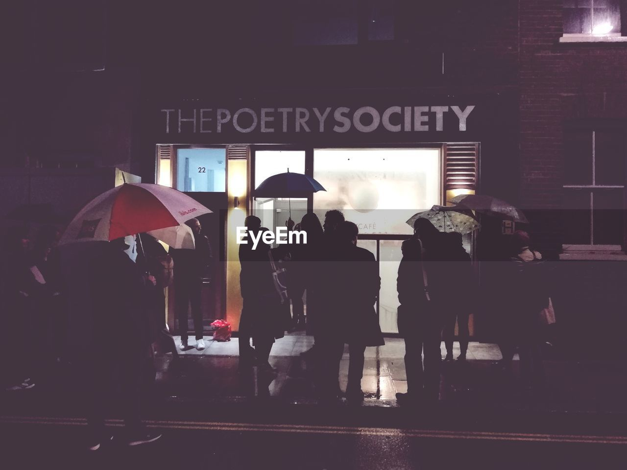 city, architecture, built structure, group of people, men, umbrella, street, building exterior, real people, walking, protection, people, city life, transportation, communication, text, sign, women, lifestyles, dark, rain, waiting