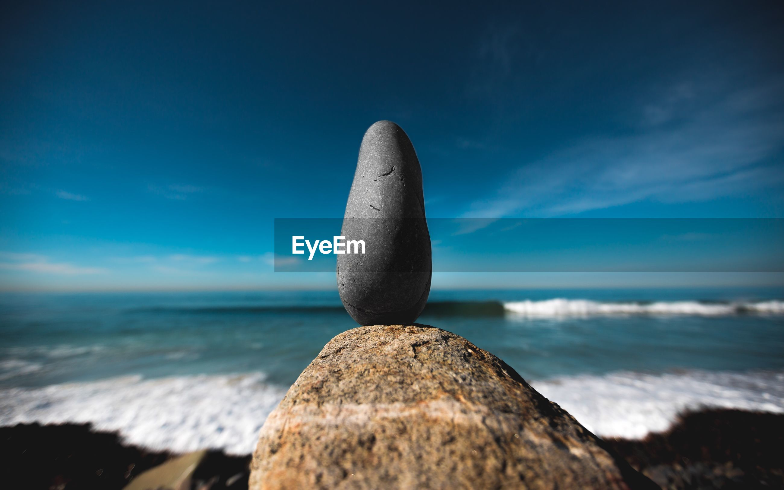 Close-up of rock on beach against blue sky