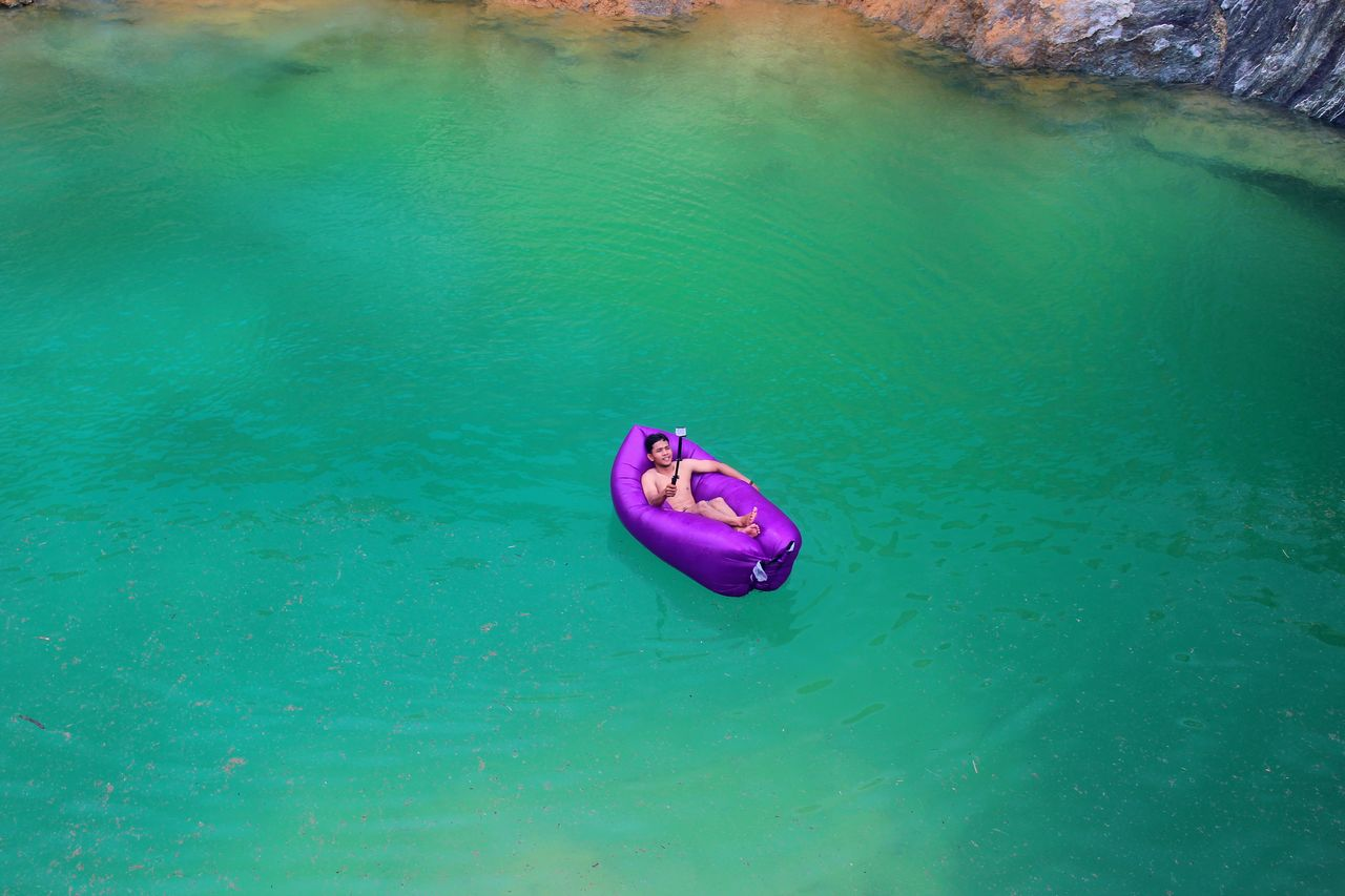 High angle view of man taking selfie while lying in inflatable on sea