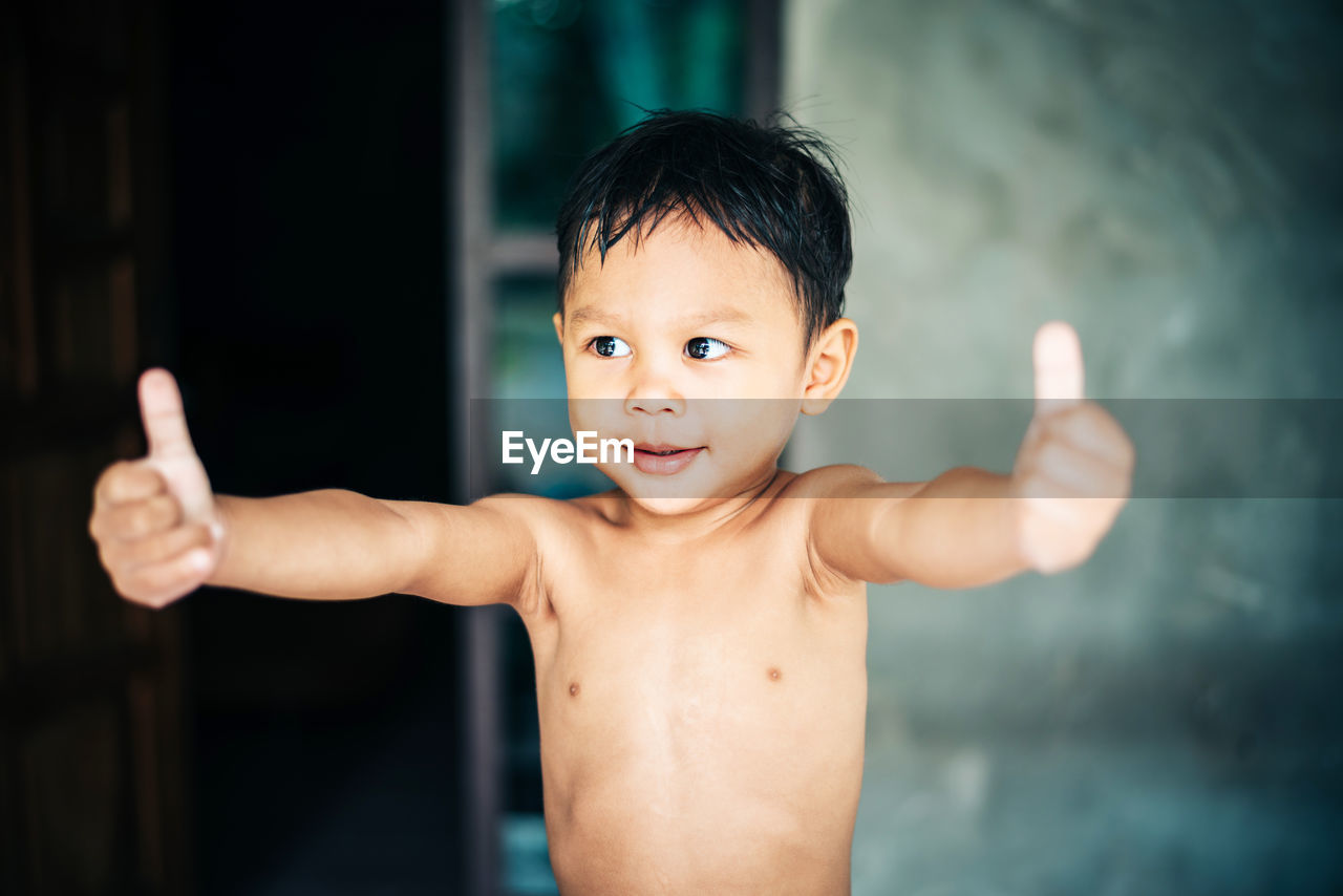 Shirtless boy showing thumbs up while standing at home