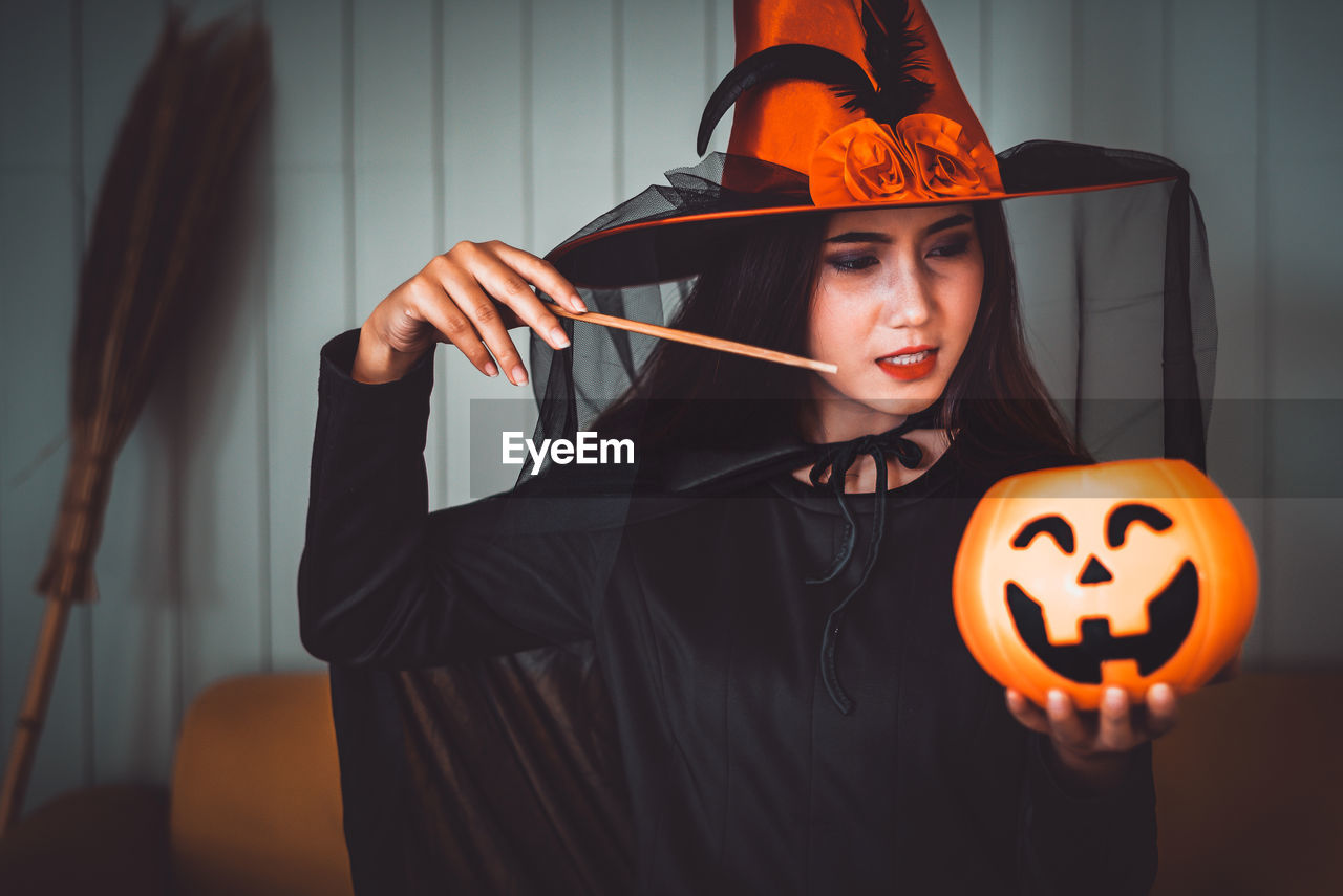 one person, halloween, indoors, real people, holding, witch, jack o' lantern, front view, celebration, lifestyles, pumpkin, young adult, focus on foreground, leisure activity, clothing, smiling, illuminated, hat, women