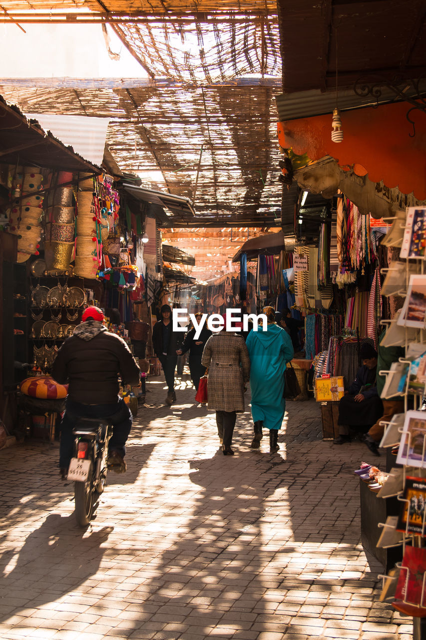 real people, market, retail, group of people, city, built structure, men, architecture, women, sunlight, business, market stall, adult, rear view, people, incidental people, lifestyles, walking, shopping, building exterior, store, street market, outdoors