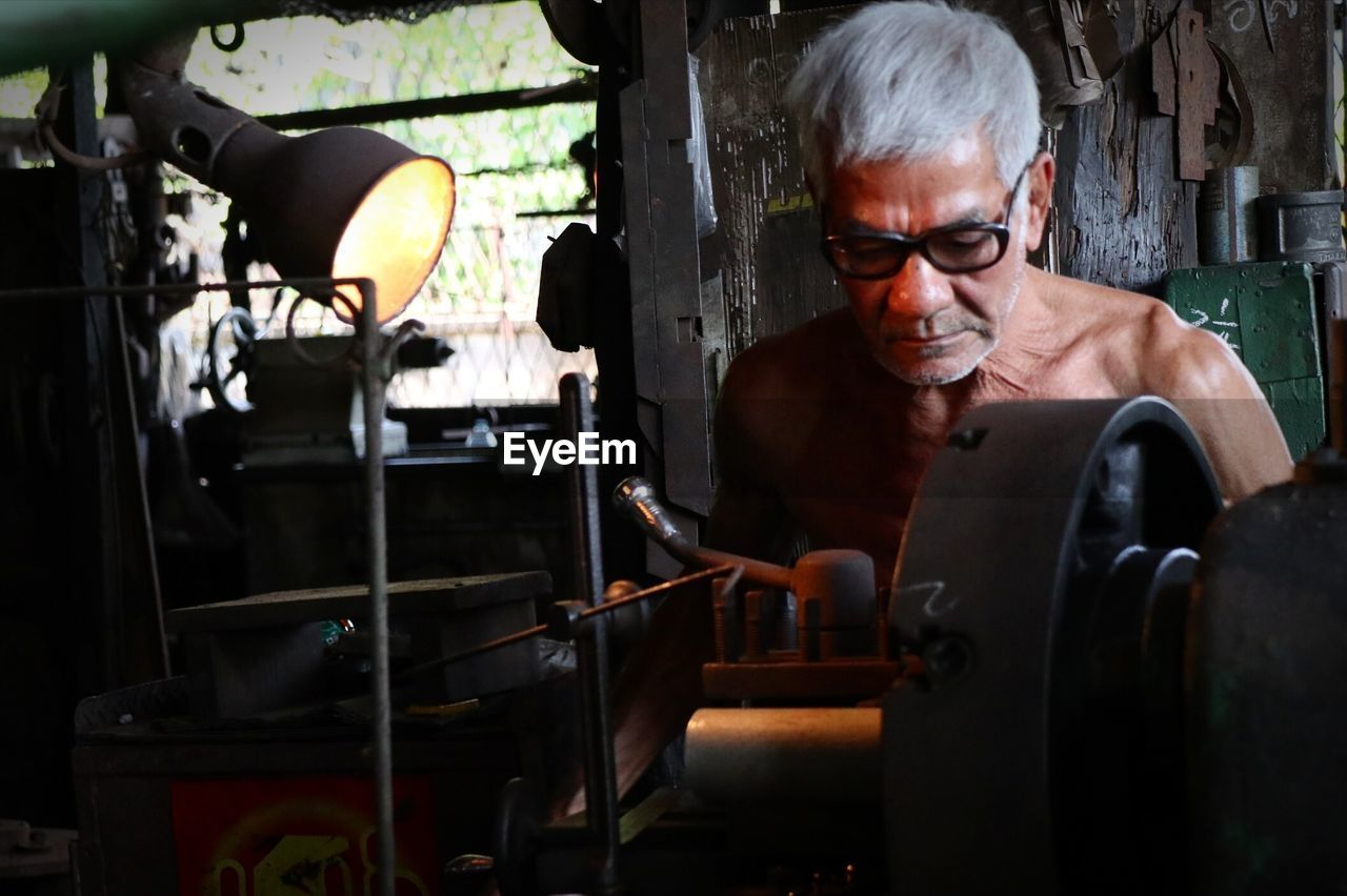 Close-Up Of Senior Man Working In Factory