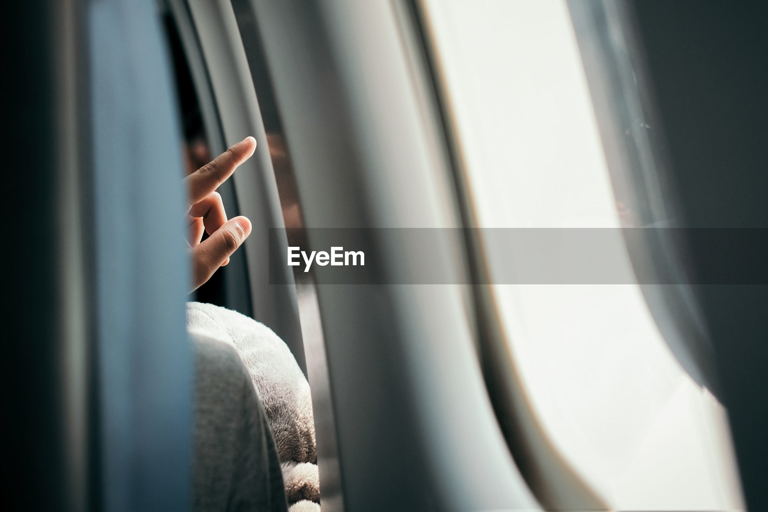 Close-up of woman pointing in airplane