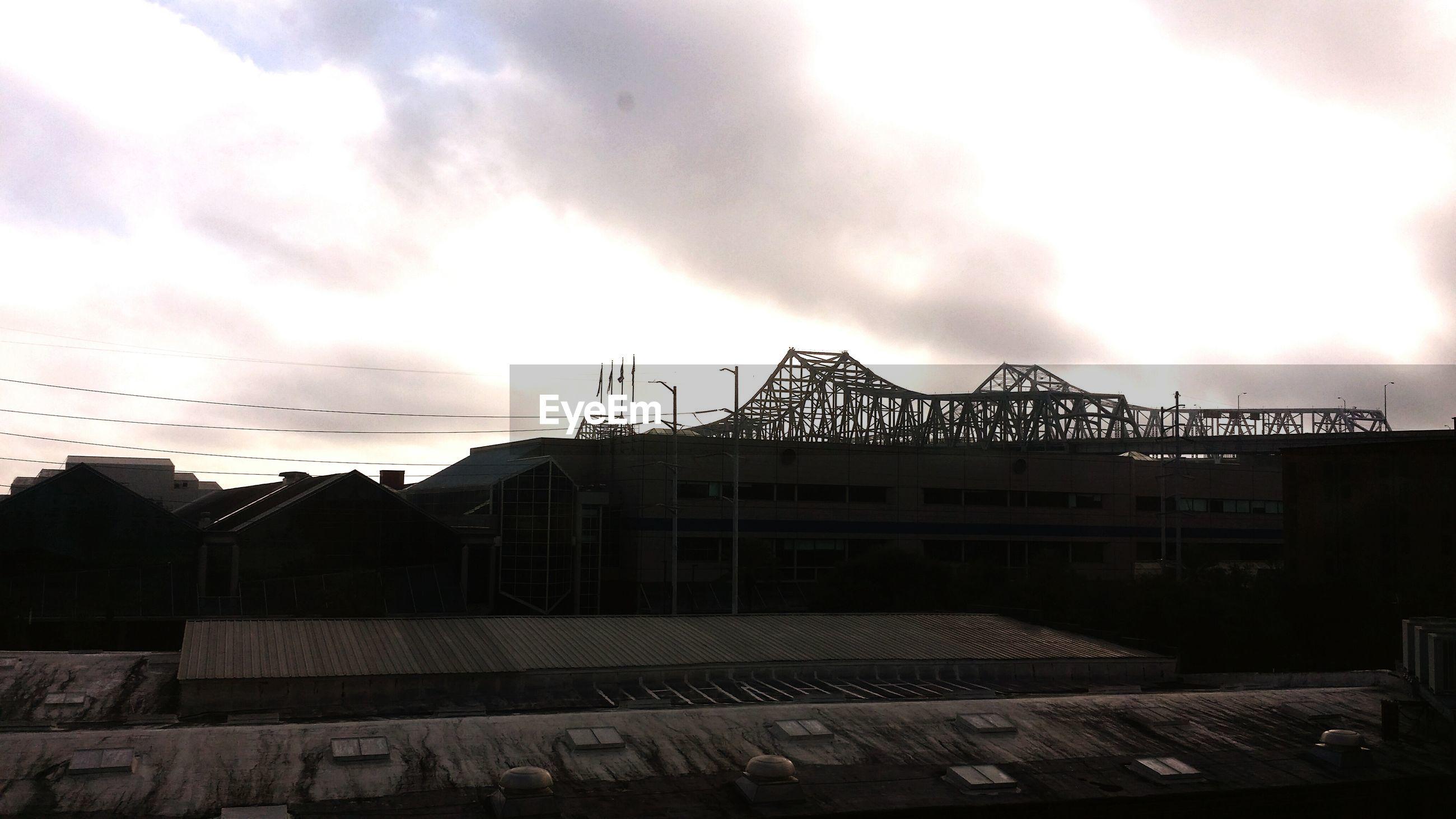 sky, architecture, built structure, building exterior, cloud - sky, cloudy, sunset, low angle view, silhouette, dusk, weather, cloud, overcast, crane - construction machinery, construction site, outdoors, bird, storm cloud, house, building