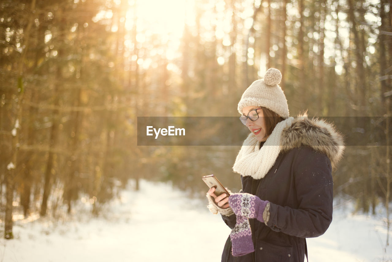 Young Woman Using Mobile Phone On Snow Covered Field
