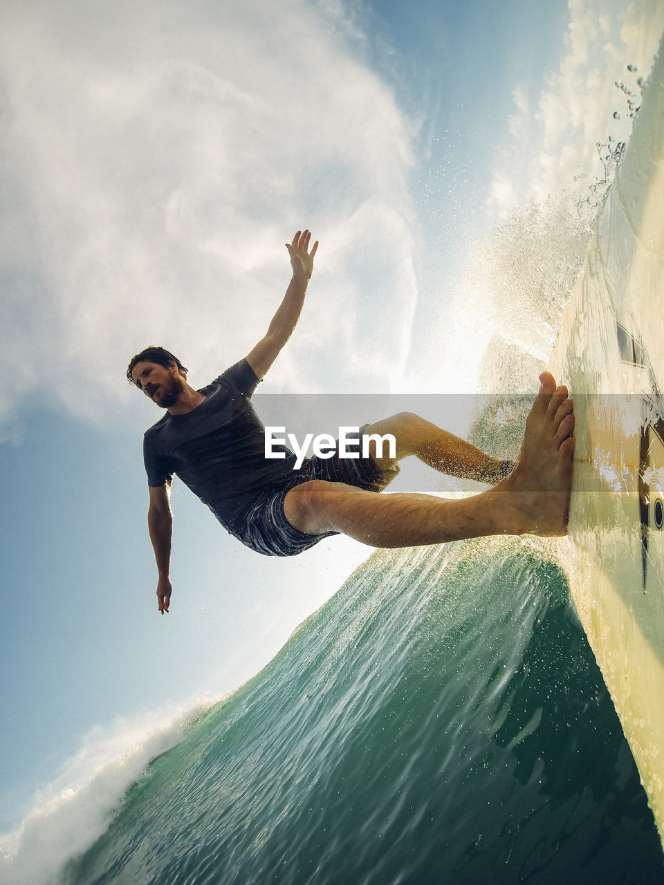 Tilt Image Of Man Surfing On Sea Against Sky