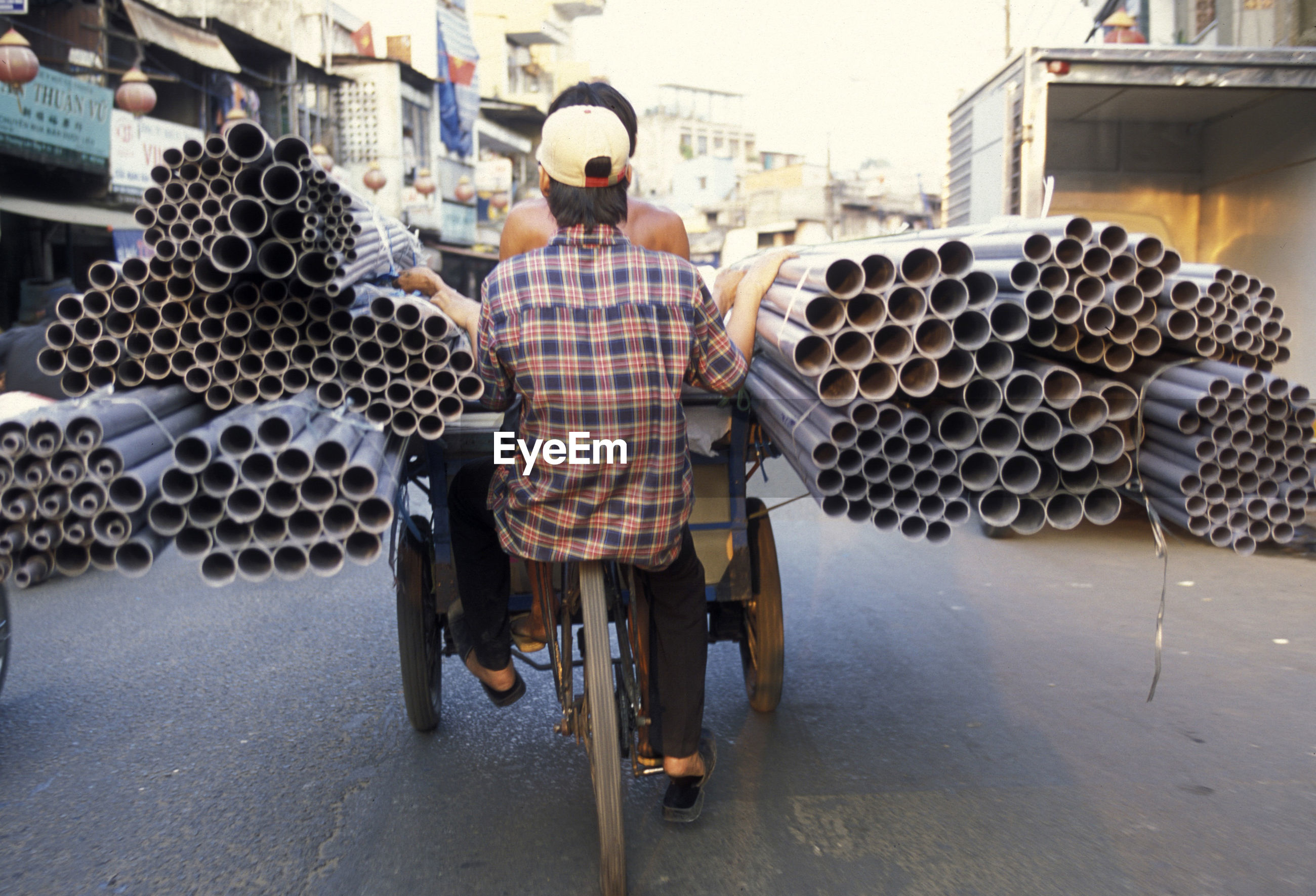 Rear view of people in tricycle while carrying pipes on street