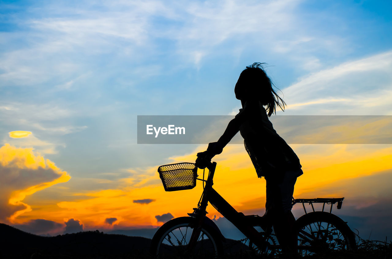Silhouette Girl Riding Bicycle Against Sky During Sunset