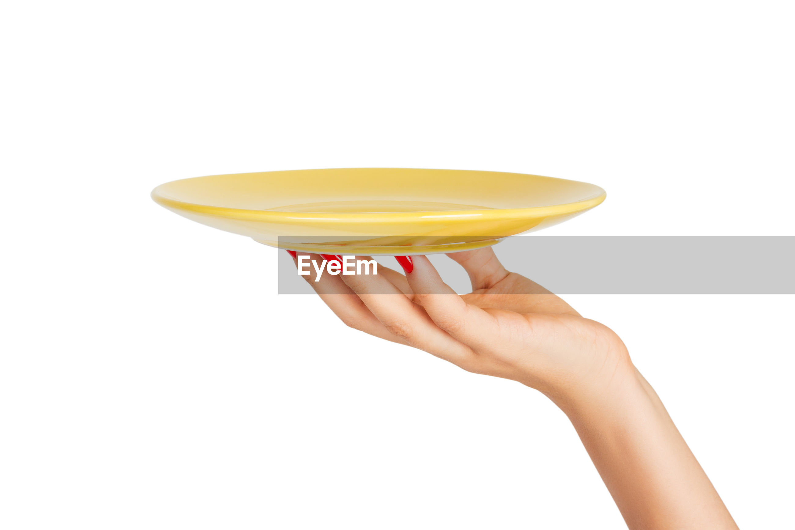Cropped hand of woman holding empty plate against white background