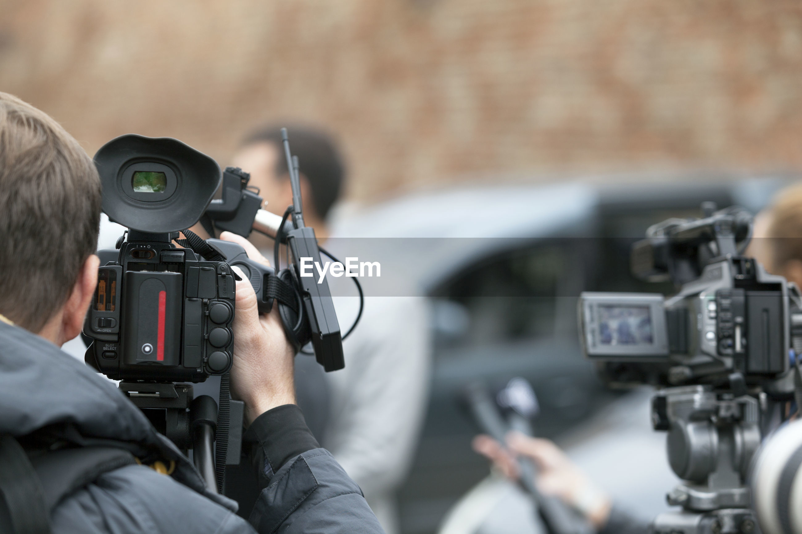 Rear view of journalist filming media event with television camera