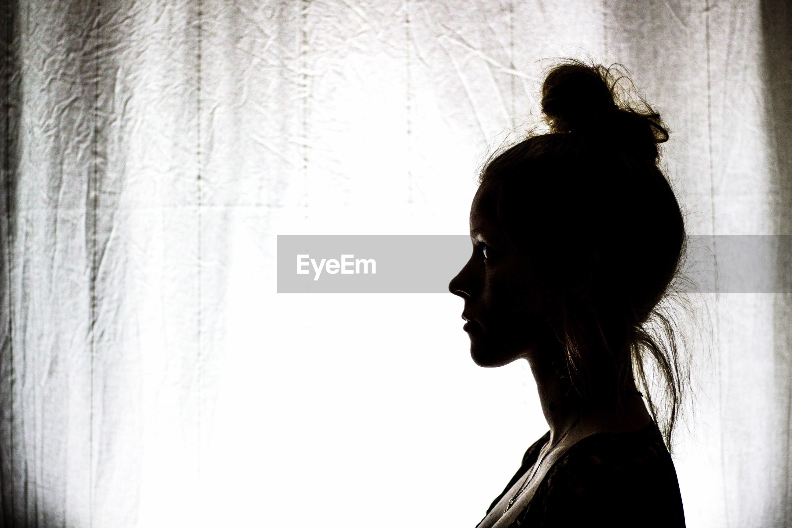 Profile view of thoughtful young woman standing by window curtain