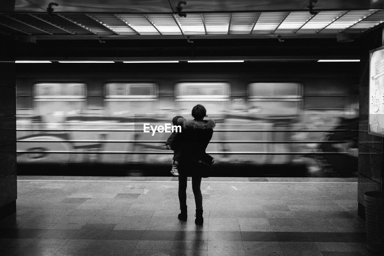 blurred motion, transportation, real people, full length, men, mode of transport, motion, railroad station platform, public transportation, railroad station, lifestyles, illuminated, indoors, women, day, adult, people